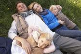 Ung familj liggande tillsammans på gräs — Stockfoto