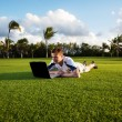 Stock fotografie: Young man whith notebook on the green field