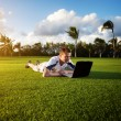 Young man whith notebook on the green field — Stock Photo