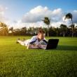 在绿色的原野上的年轻男子连笔记本 — 图库照片