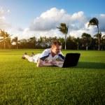 Молодой человек whith ноутбук на зеленом поле — Стоковое фото