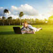 Young man whith notebook on the green field - Stock Photo