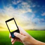 Мобильный телефон в руки и страны закат — Стоковое фото