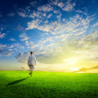 One man and field of spring grass and sunset — Stock Photo #4493856