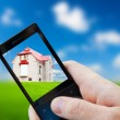 Cell phone in hand and house — Stock Photo