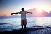 Happy young man in sea and sunrise — Stock Photo