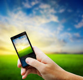 Cell phone in hand and country sunset — Stock Photo