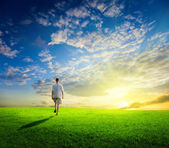 One man and field of spring grass and sunset — Stock Photo