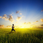 Sunset and running young man — Stock Photo