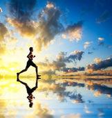 Running man sunset and water — Stock Photo