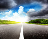 Road black clouds and sun — Stock Photo