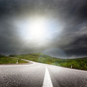 Road and black clouds — Stock Photo