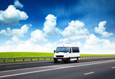 Van on road and perfect summer day — Stok fotoğraf