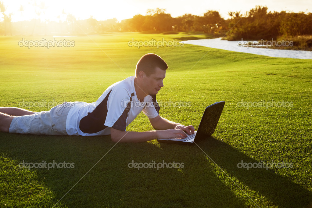 Young man whith notebook on the green field and sunset — Stock Photo #4492098