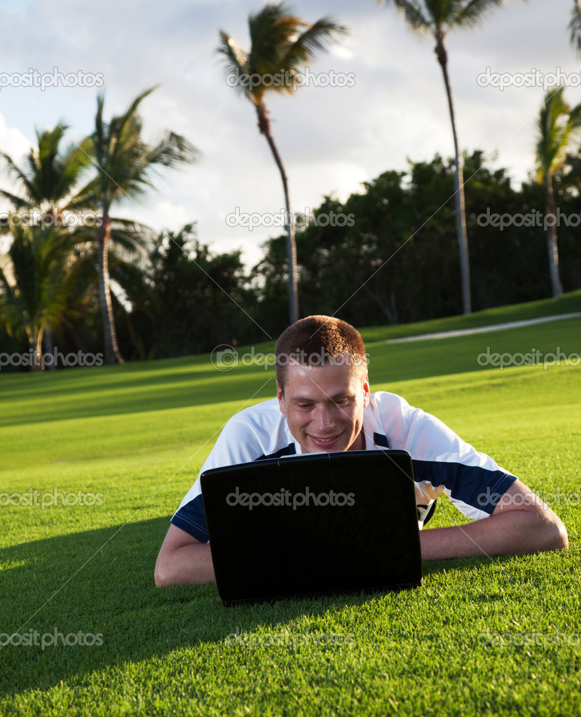 Young man whith notebook on the green field and sunset — Stock Photo #4492101