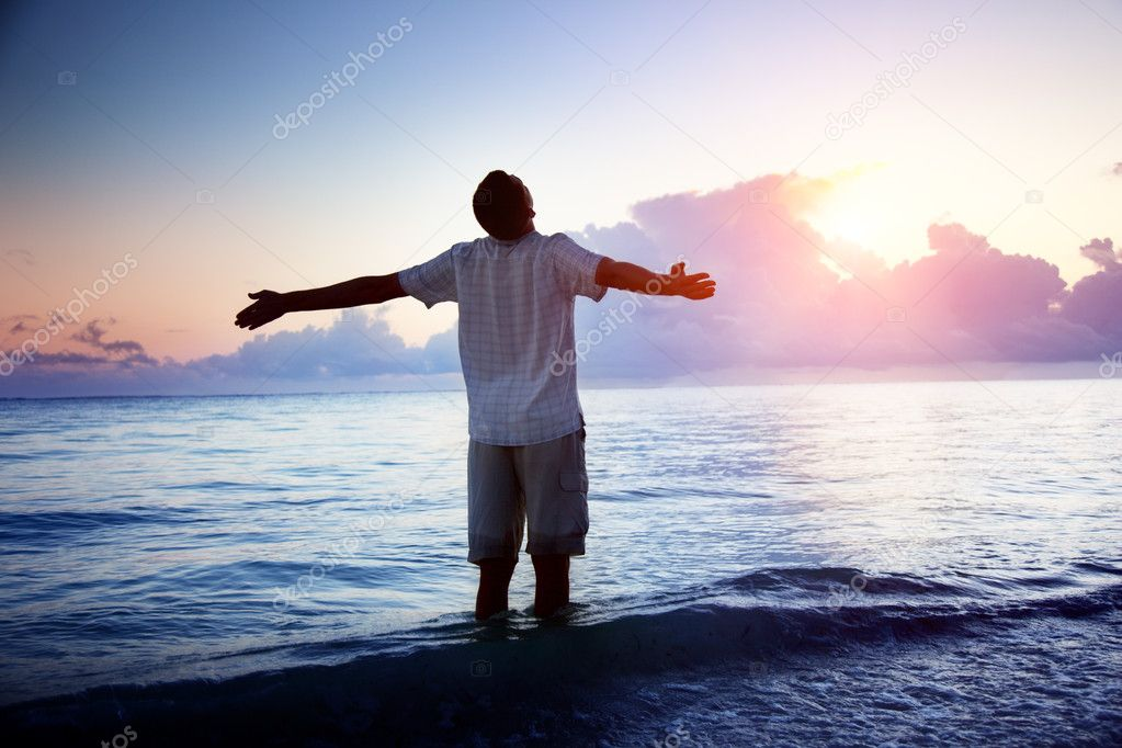 Happy young man in sea and sunrise — Lizenzfreies Foto #4492601