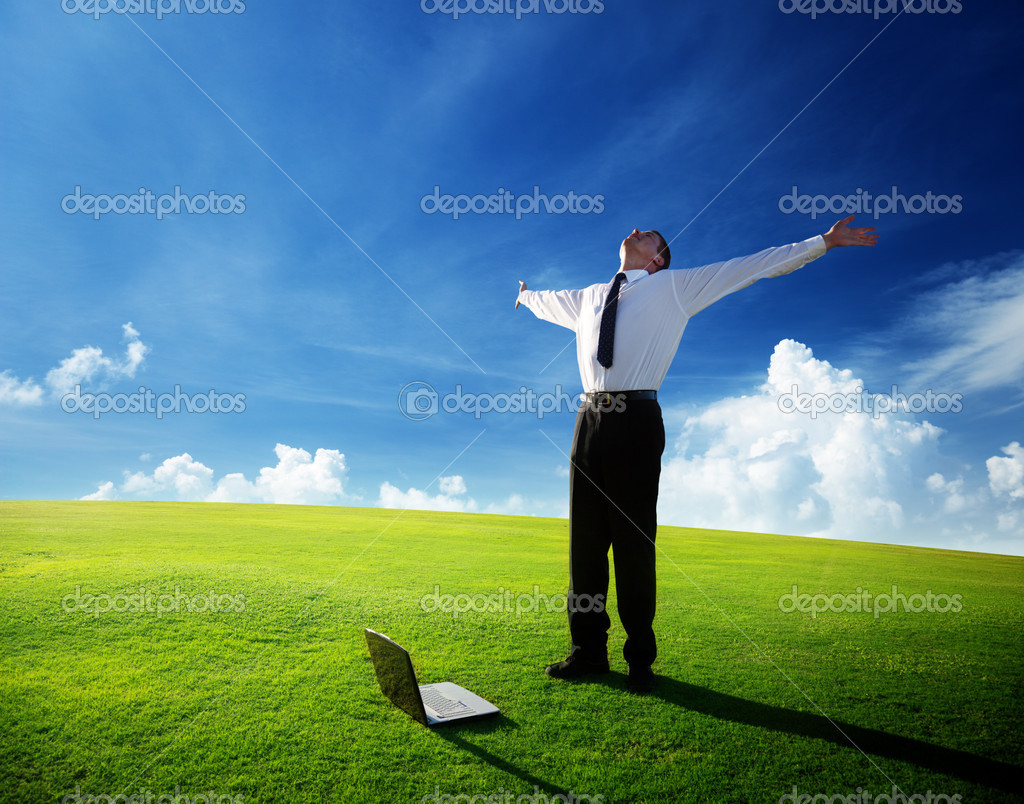 Happy young businessman on spring field — Stockfoto #4493372