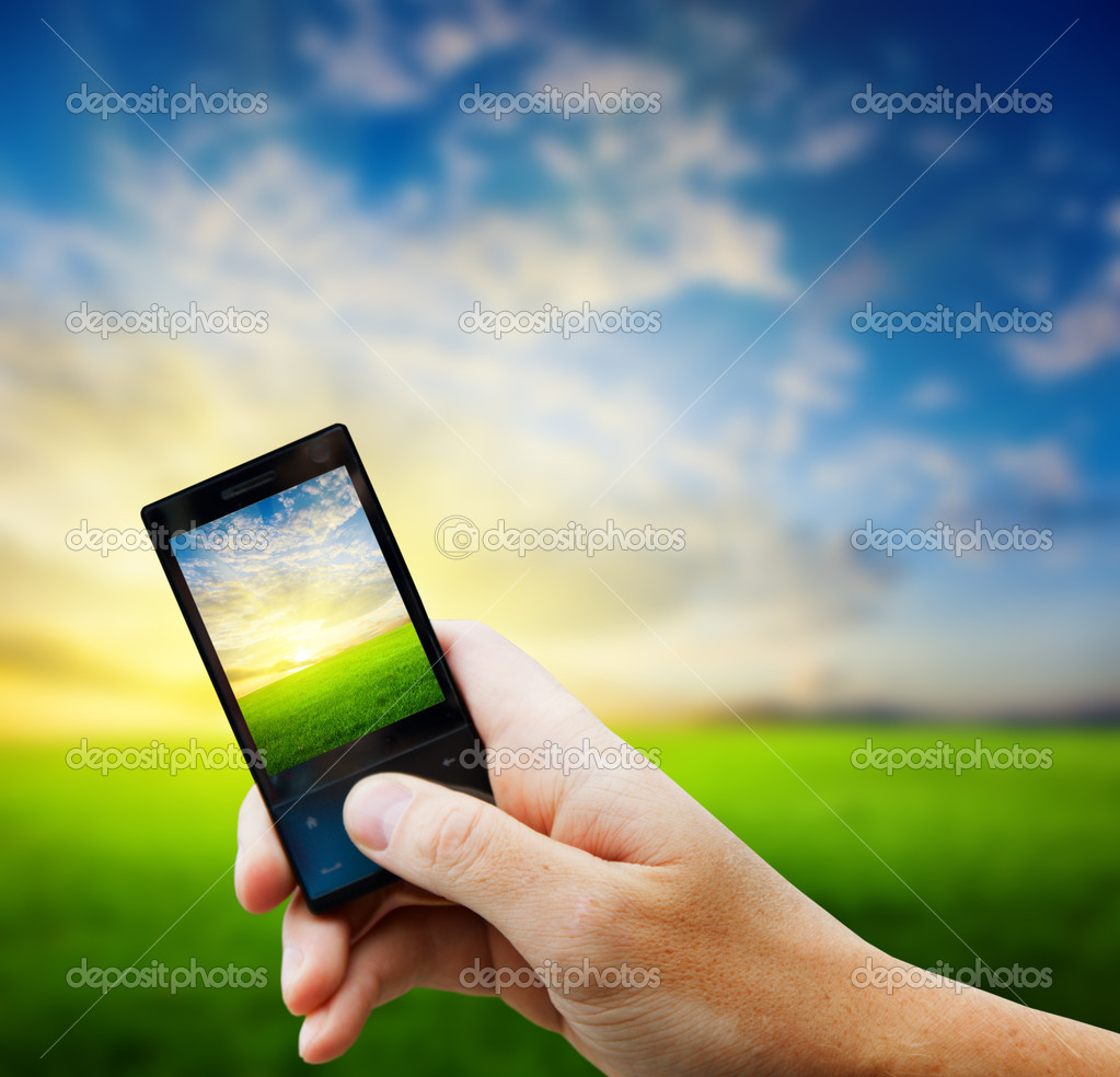 Cell phone in hand and country sunset — Stockfoto #4493496