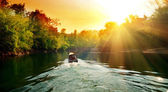 Sunset in jungle and boat — Stock Photo