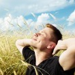 Young man rest on wheat field — Stock Photo