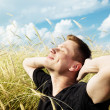 Royalty-Free Stock Photo: Young man rest on wheat field