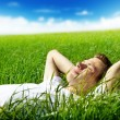 Young man in spring grass — Stock Photo