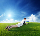 Young man use a notebook on green field — Stock Photo