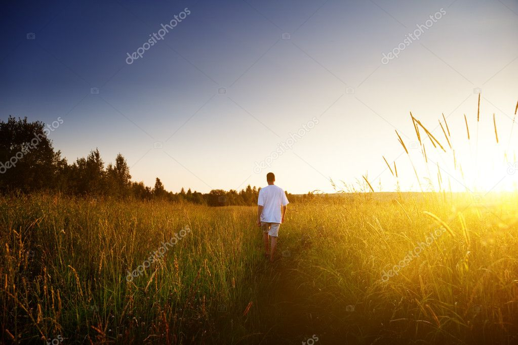 Young man walking on field — Stock Photo #4621882