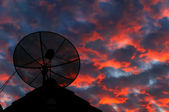 Satellite dish silhouette on the roof in evening sky. — Stock Photo