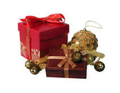 Red gift box against gold Christmas-tree decorations — Stock Photo