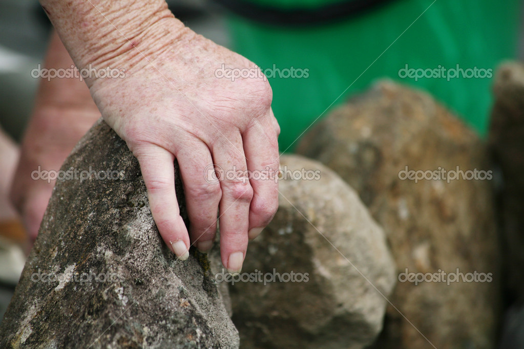 Living with pain series. Hands of a senior woman with rheumatoid arthritis moving rocks in the garden — Stock Photo #4577116