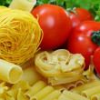 Different varieties of pasta, ripe tomatoes and greens. - Stock Photo