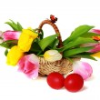 Easter eggs and a basket with colorful tulips. — Stock Photo
