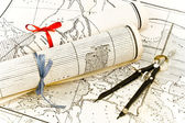 Old Maps in rolls with ribbons and compass — Stock Photo