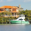 Luxury home and boat on the water - Stock Photo