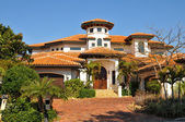 Spanish style home with tower, multiple roofs — Stock Photo