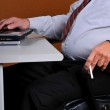 Business man at desk holding a cigarette — Stock Photo