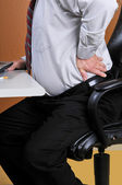 Back pain while working at the office — Stock Photo