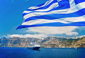 Greek Flag in front of Santorini — Zdjęcie stockowe