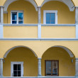 Arcade of a yellow baroque House - Stock Photo