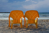 Couple of plastic beach chairs facing to sea — Stock Photo