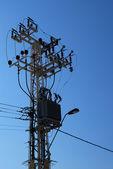 Elektrisk transformator på pelare över blå himmel — Stockfoto
