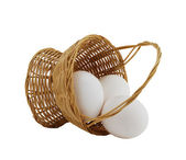Three white eggs spilled from straw interwoven basket — Stock Photo
