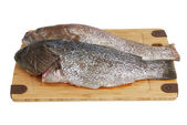 Two scaled grouper fish on bamboo cutting board — Stockfoto