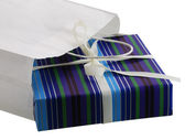 Present wrapped in striped blue paper sticking out from white ba — Stock Photo