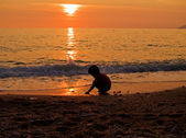 Kid on the beach at sunset — Stock Photo
