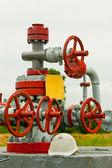 Helmet lying next to oil valves — Stock Photo