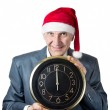Old man in Christmas hat holding a big clock isolated on white — Stock Photo