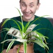 Old man holding money plant — Stock fotografie