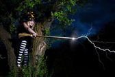 Witch strikes lightning from the broomstick — Stock Photo